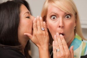 Two Friends Whispering Secrets in the Ear.