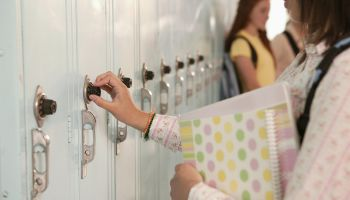 Teenage girl unlocking school locker