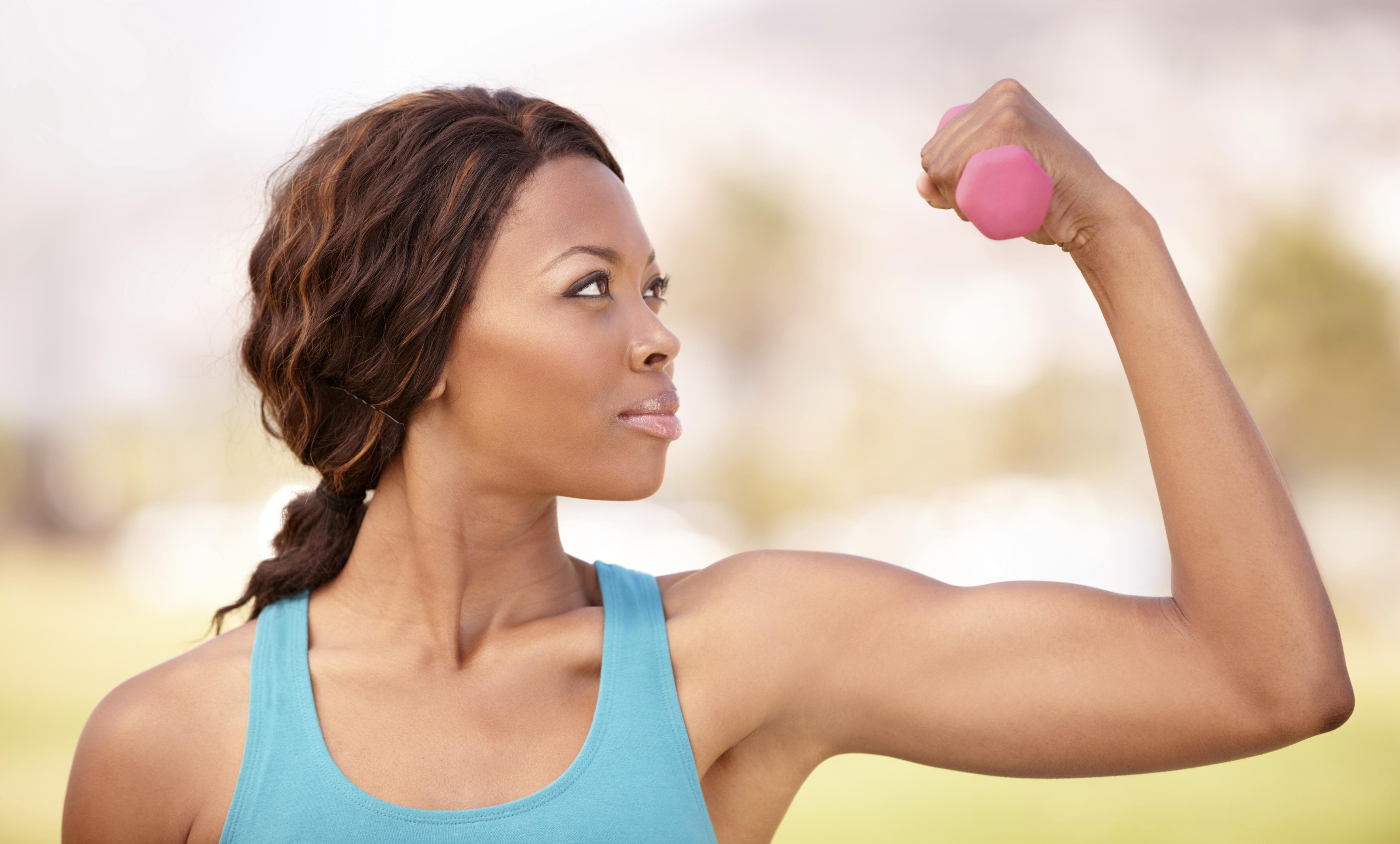 A beautiful african-american woman doing weight training outdoors