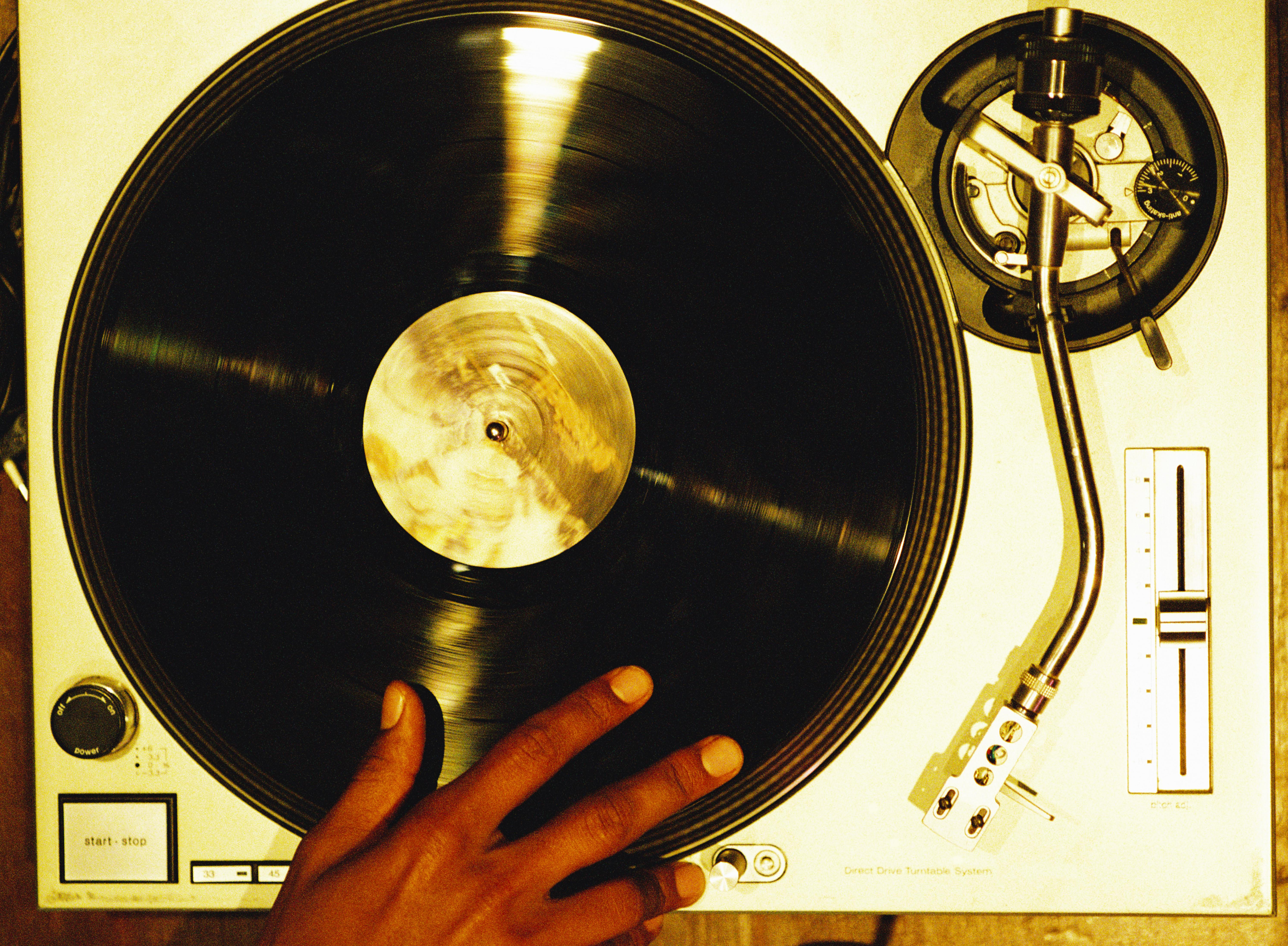 high angle close-up of a hand scratching a vinyl record on a turntable
