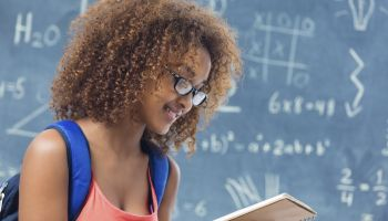 High school student reading homework assignment in front of blackboard