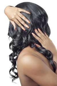 Beautiful woman with hands on her curly hair, back view, isolated on white