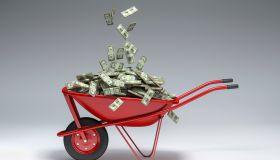 Dollars falling into red wheelbarrow