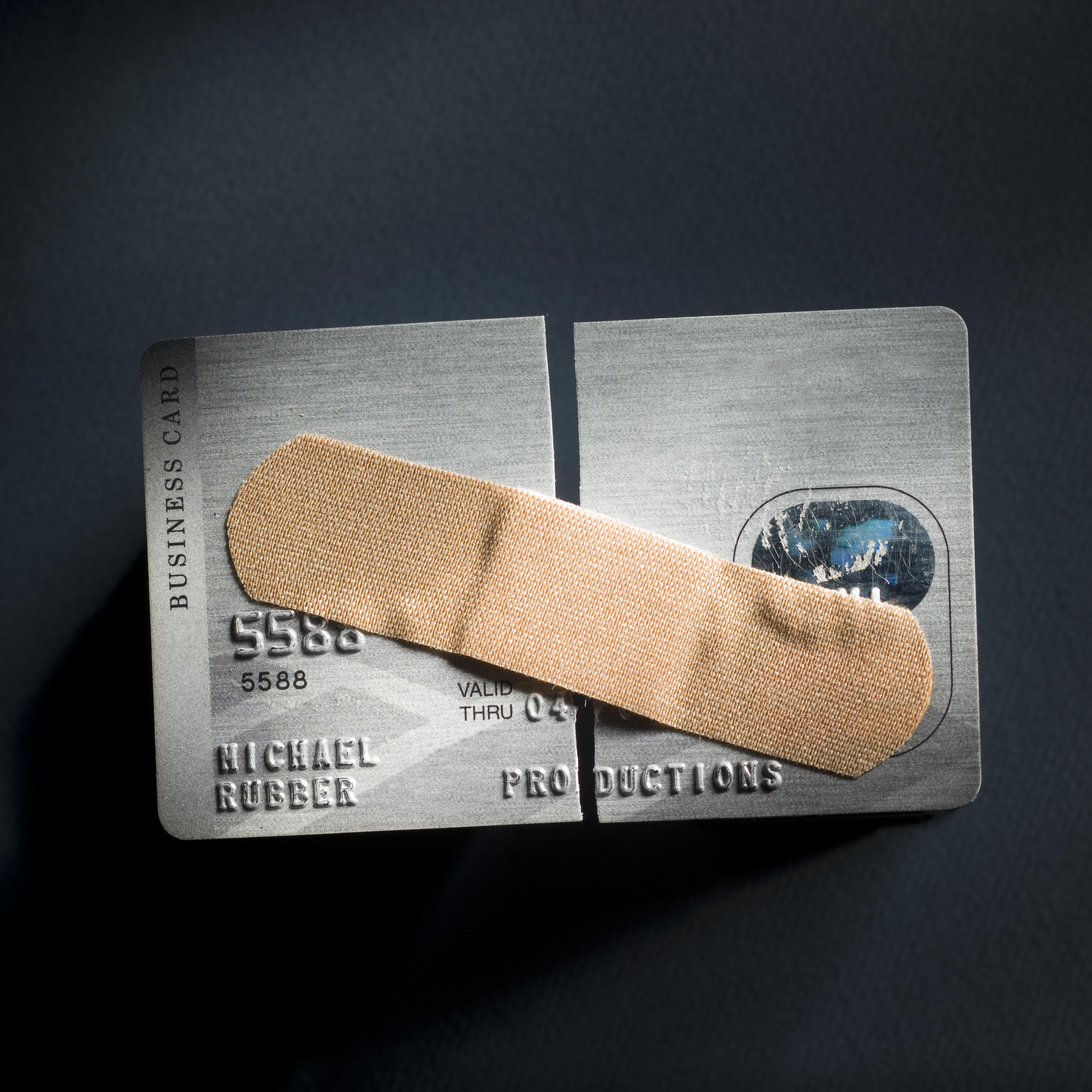 credit card cut in half with a band-aid holding it together