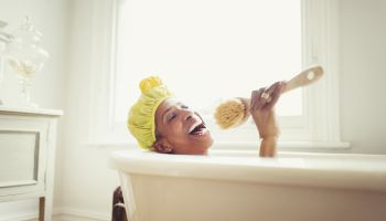 Playful mature woman singing into loofah brush in bathtub