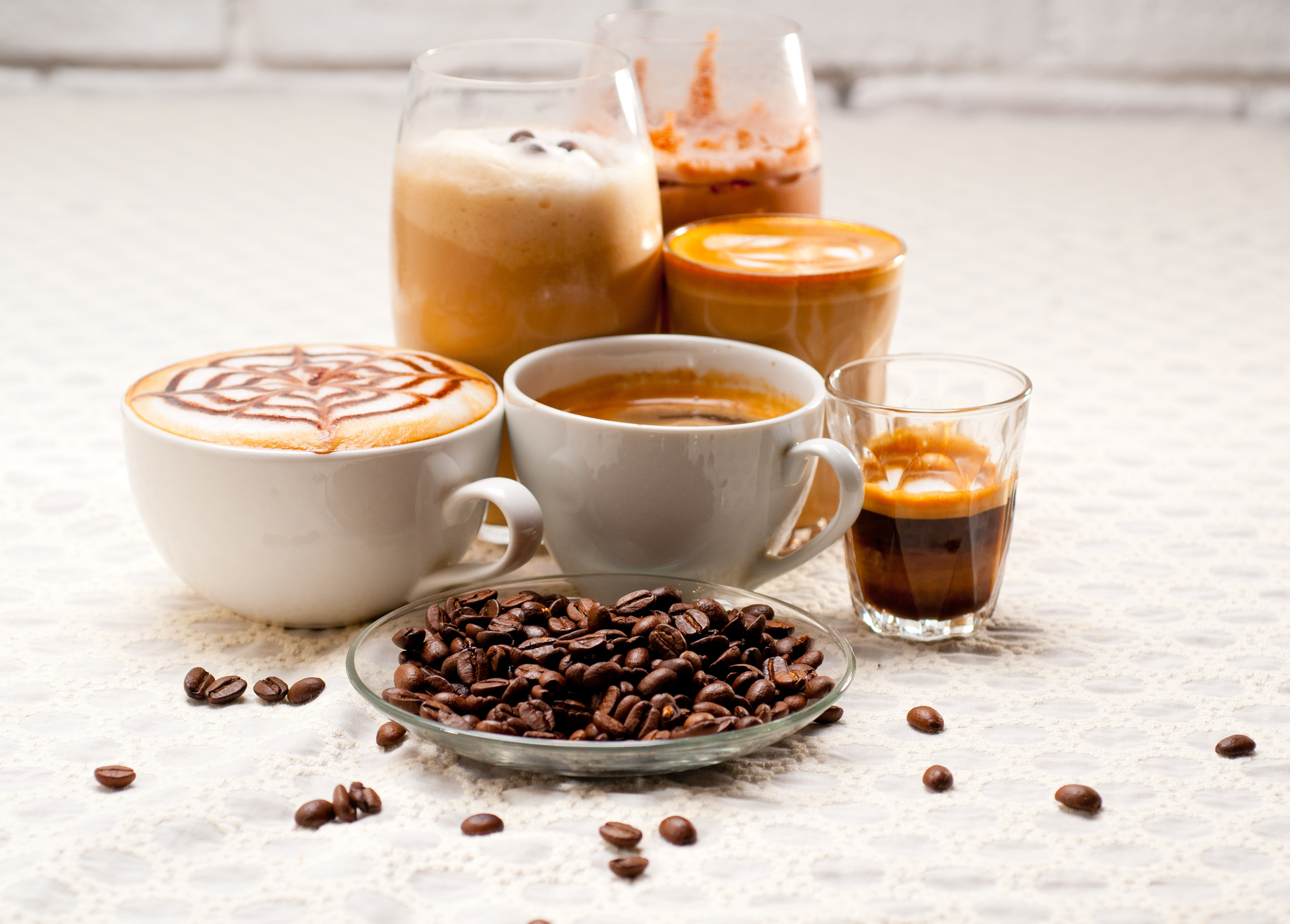 Close-Up Of Coffees With Roasted Coffee Beans Served On Table