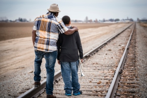 Father and son standing on train track with trumpet