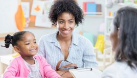 African American mom talks with teacher during conference