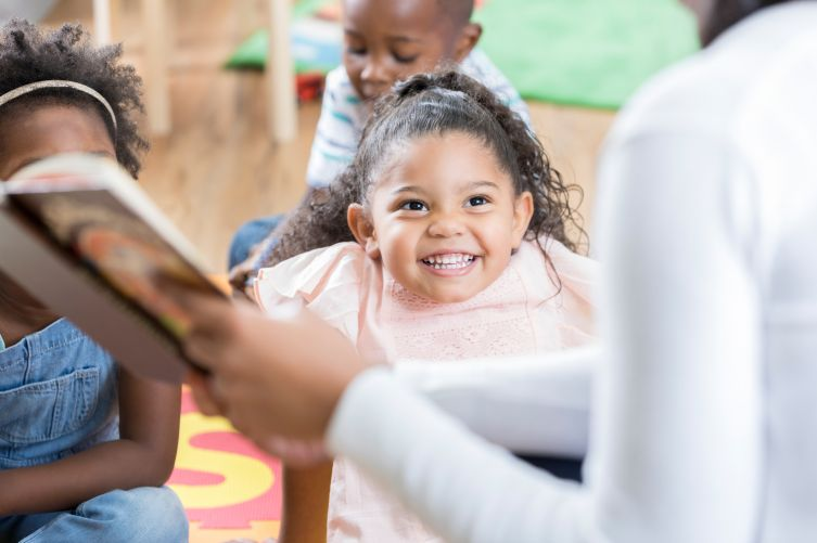 Grinning preschool age girl enjoys story time