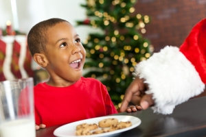Surprised little boy sees Santa taking Christmas cookie