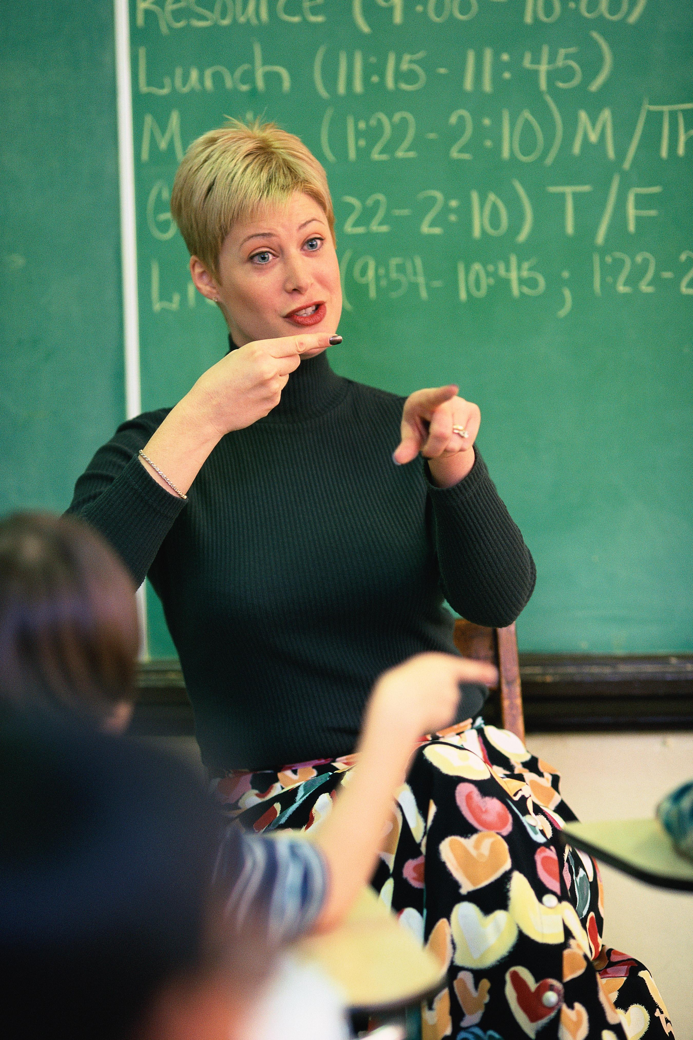 Teacher talking and pointing at front of classroom