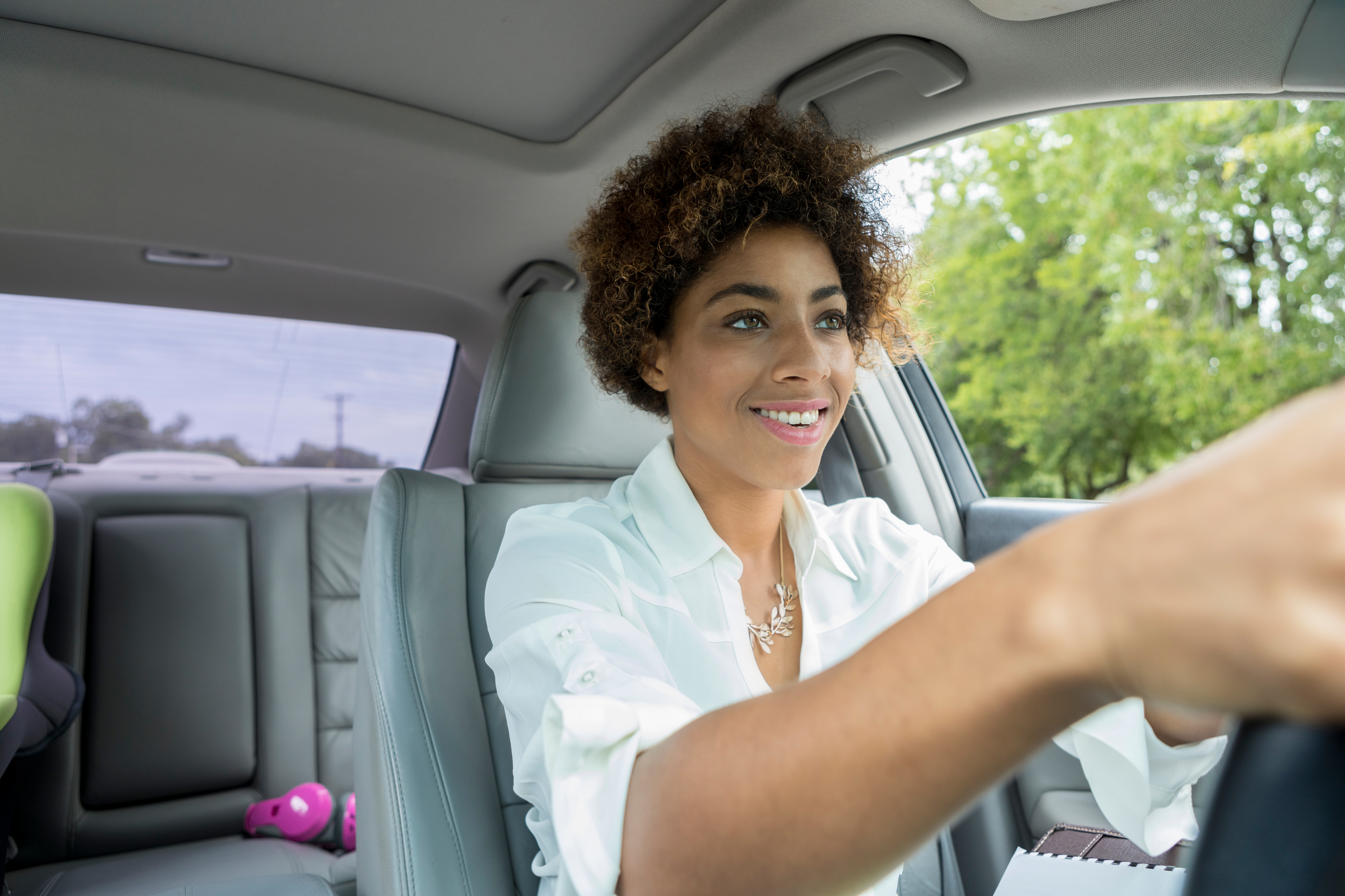 Smiling young woman driving her car on a sunny day