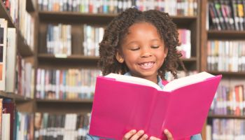 African descent little girl in school library reading book.