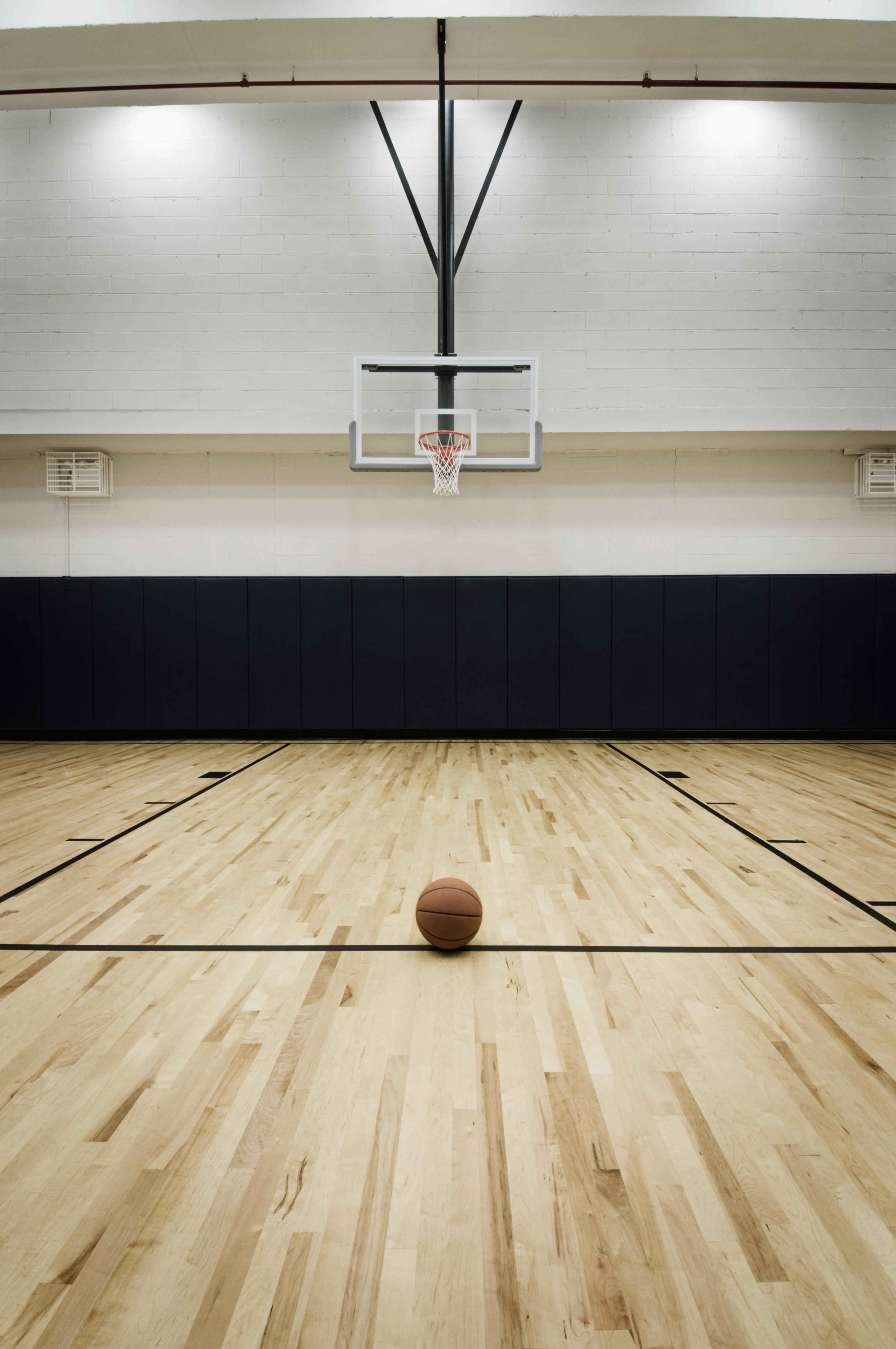 A basketball sits on the free throw line.