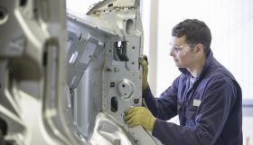 Apprentice wearing boiler suit inspecting car body parts in car plant