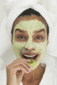 Portrait of a young woman wearing a facial mask eating a slice of kiwi