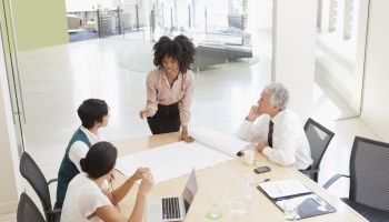 Project discussions amongst employees in boardroom