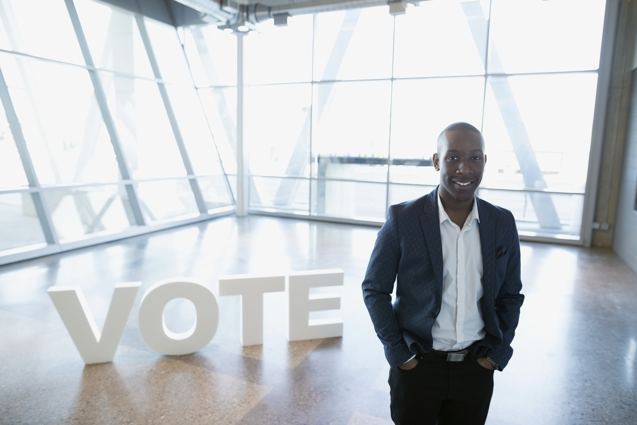 Portrait smiling young businessman near Vote text
