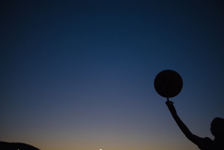 Silhouette Boy Holding Basketball Against Sky During Sunset