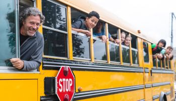 Portrait of bus driver and students on the school bus