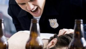 Police officer arresting man lying down with beer bottles