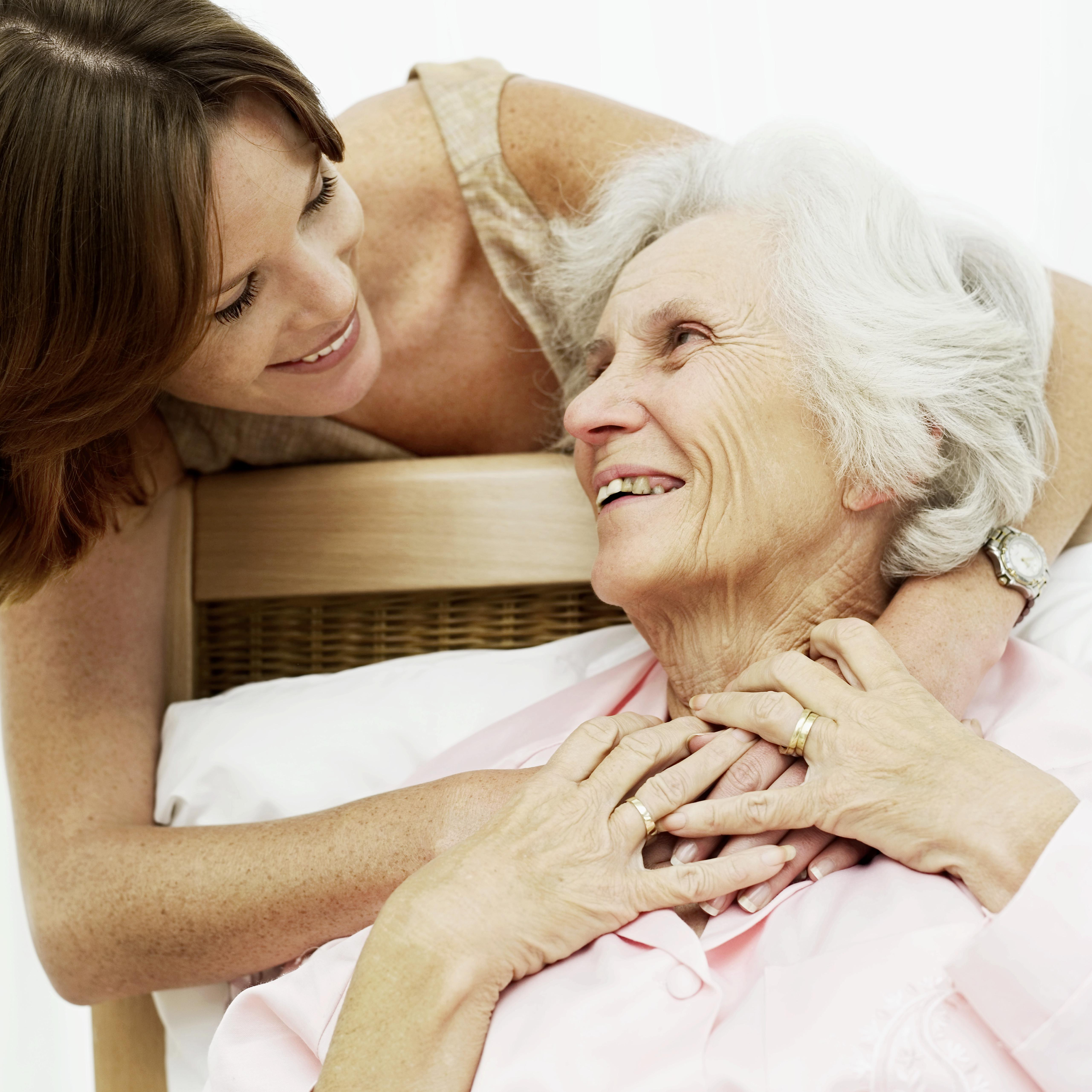 woman smiling and holding an old woman in bed