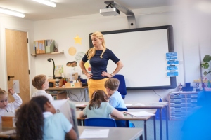 Teacher with hands on hips in front of class at primary school