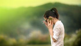 Woman smoking and talking on cell phone outdoors