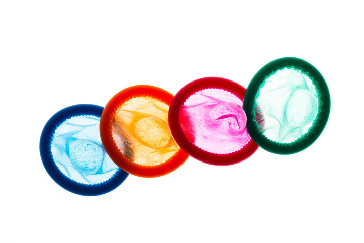 High Angle View Of Multi Colored Condoms Against White Background