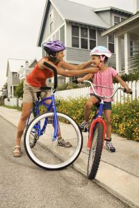 Woman adjusting daughter's safety helmet