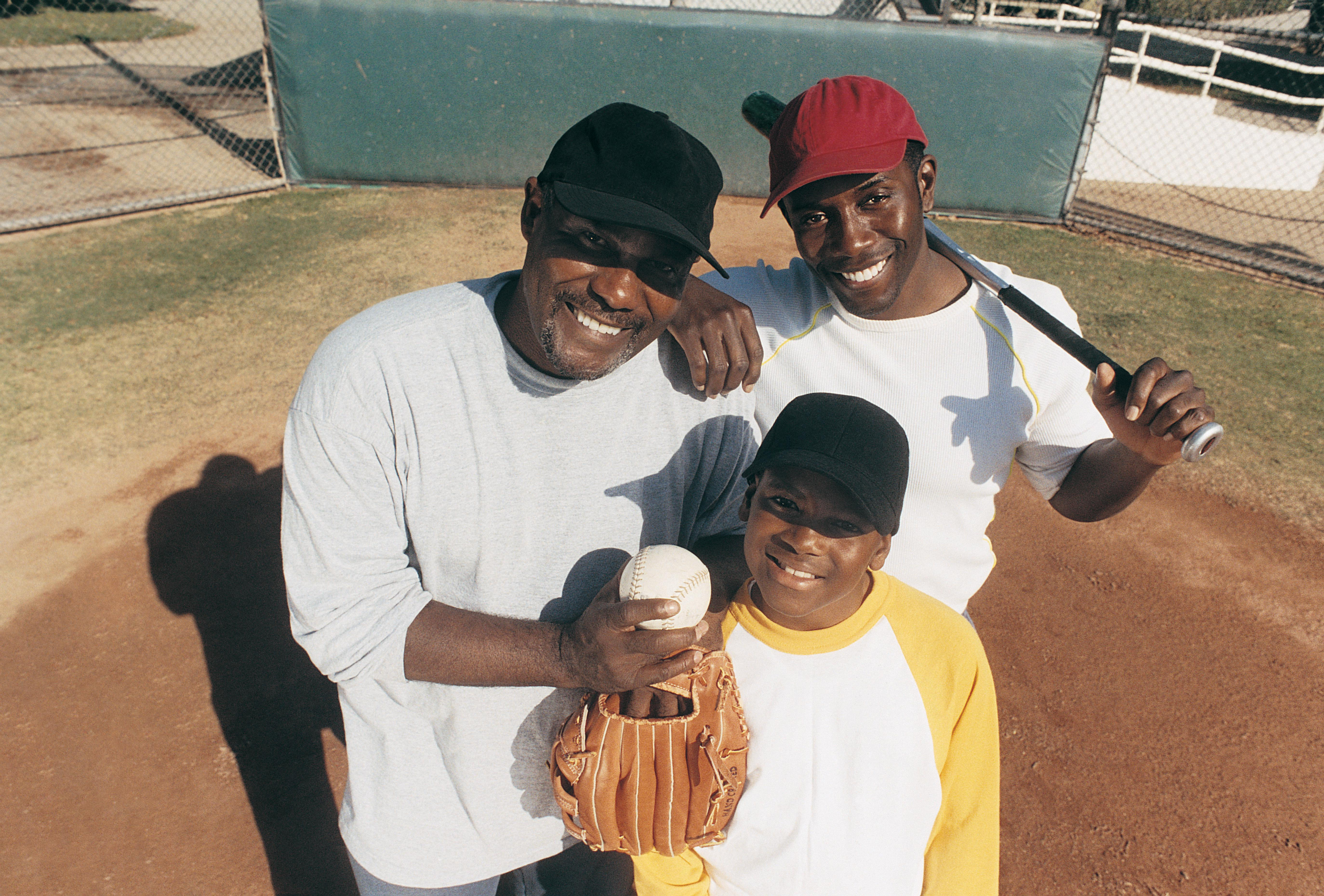Portrait of a Father Standing With His Two Sons on a Baseball Field