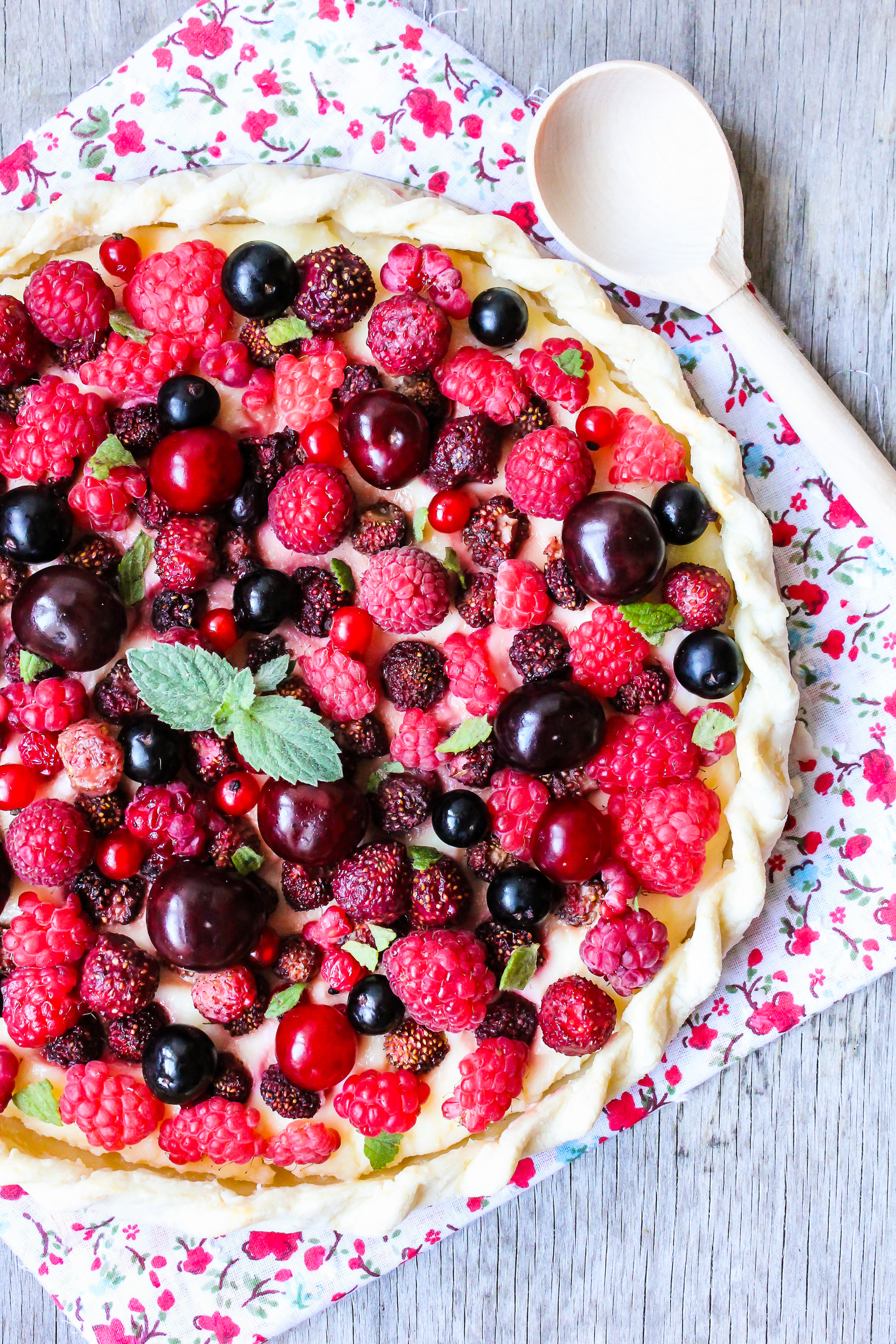 Homemade puff pastry sweet pie with fresh cherry, raspberry, black currant and strawberry with cream cheese decorated with fresh mint on a wooden table, selective focus