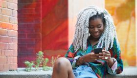 Smiling Black woman texting on cell phone