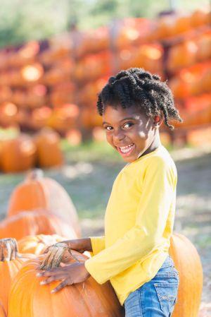 Little African-American girl in a pumpkin patch