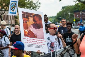 Rally participants hold signs near the site of Eric Garner's...