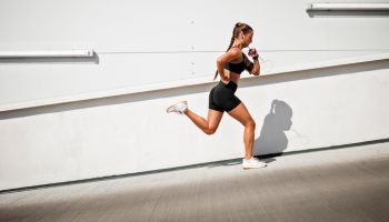 Young sportswoman running outdoors on a sunny day