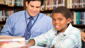 Teacher, mentor helps elementary-age schoolboy with homework.