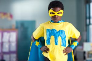 African American boy wearing superhero costume in classroom