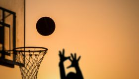 Silhouette Person Taking A Shot By Basketball Hoop Against Sky During Sunset