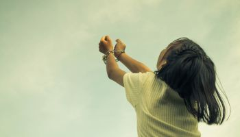 Girl Handcuffs Against Cloudy Sky