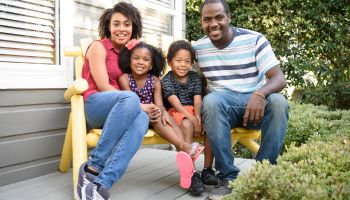 Young African American family sitting on bench outside house