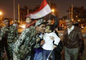 An Egyptian boy kisses a soldier as anti