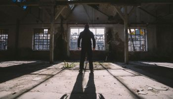 Adult man standing inside some large, dark, spooky,abandoned building illuminated with sunlight through window