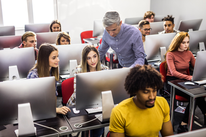 Mid adult professor assisting young students during a class at computer lab.