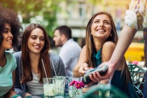 Group of young women paying with credit card in bistro
