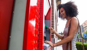 Smiling woman pushing credit card at cash dispenser