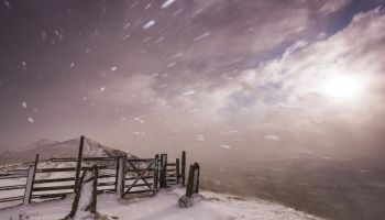 Severe blizzard conditions over Mam Tor at sunrise in the Peak District National Park, Derbyshire