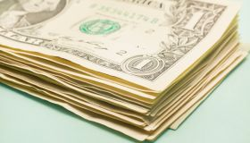 Stack of American Dollar banknotes on turquoise background