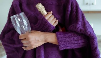Woman Holds Bottle of Wine and Glass
